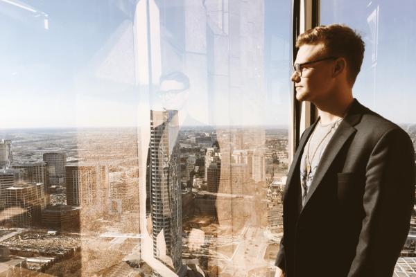 Homme travaillant sur le référencement, jetant un regard sur la ville à travers la fenêtre